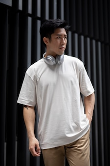 Porträt eines gutaussehenden asiatischen mannes, der mit kopfhörern im freien in der stadt posiert