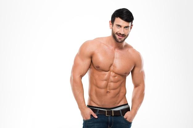 Porträt eines gutaussehenden athletischen mannes mit nacktem torso, der lokal auf einer weißen wand steht