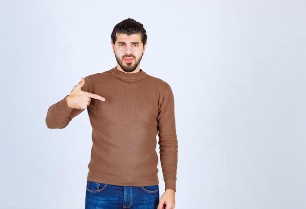 Porträt eines gutaussehenden bärtigen jungen mannes im braunen pullover, der sich selbst steht und zeigt. foto in hoher qualität
