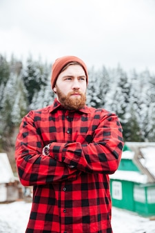 Porträt eines gutaussehenden bärtigen jungen mannes in einem karierten hemd mit rotem hut, das mit verschränkten armen steht
