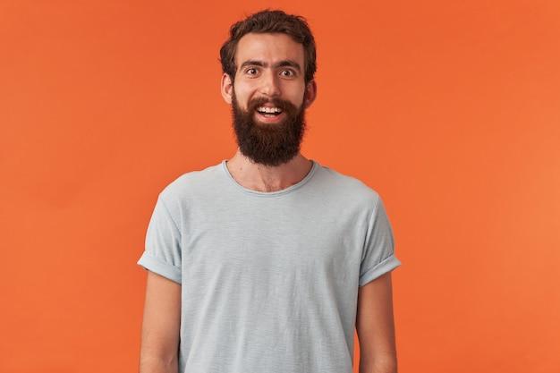 Porträt eines gutaussehenden bärtigen jungen mannes mit braunen augen im weißen t-shirt der freizeitkleidung ist, glückliches, glückliches lächeln auf sie