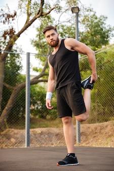 Porträt eines gutaussehenden bärtigen sportlers, der draußen die beine ausdehnt