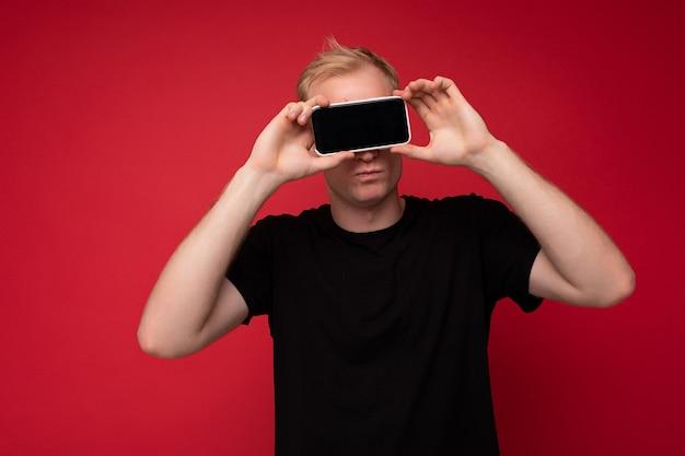 Porträt eines gutaussehenden blonden jungen mannes mit schwarzem t-shirt, der isoliert auf rotem hintergrund steht und ein mobiltelefon hält, das smartphone in der hand mit leerem display für ausschnitt und mockup zeigt