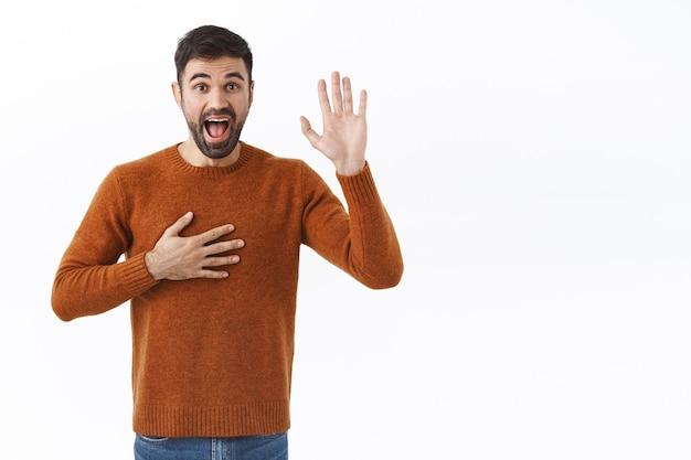 Porträt eines gutaussehenden, enthusiastischen bärtigen mannes, der schwört, die wahrheit zu sagen, die hand aufs herz zu halten und den arm zu heben, um einen eid zu geben, versprechen, gut zu sein, bitten, kandidat zu sein, versichern, dass er das beste kann, weiße wand