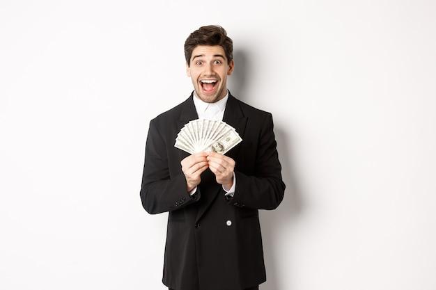 Porträt eines gutaussehenden erfolgreichen geschäftsmannes im trendigen anzug, der geld zeigt und erstaunt lächelt, geld verdienen und auf weißem hintergrund stehend