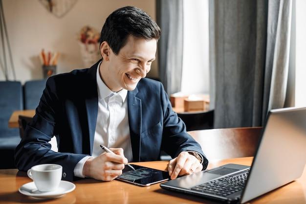 Porträt eines gutaussehenden geschäftsmannes, der auf einem tisch sitzt, der an einem laptop und einem tablet arbeitet, das lächelnd betrachtet den bildschirm des laptops.