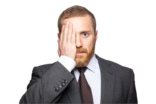 Porträt eines gutaussehenden geschäftsmannes, der ein auge mit seiner hand bedeckt, während er direkt in die kamera schaut. isoliert auf weißem hintergrund.
