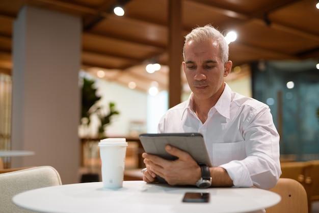 Porträt eines gutaussehenden geschäftsmannes, der im café sitzt und ein digitales tablet verwendet?