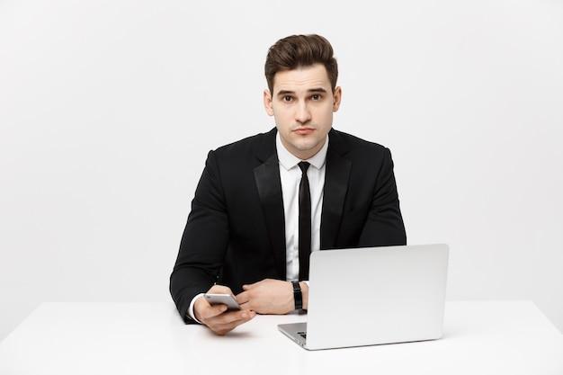 Porträt eines gutaussehenden geschäftsmannes, der smartphone hält, während er an einem computer an seinem schreibtisch arbeitet, ist er ...