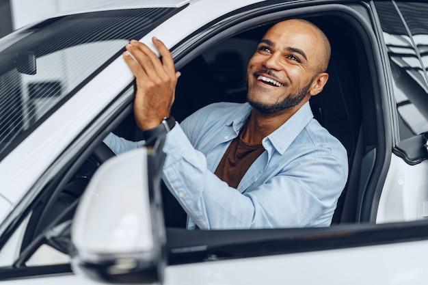 Porträt eines gutaussehenden glücklichen mannes, der in seinem neu gekauften auto sitzt