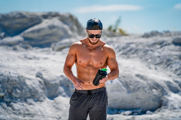 Porträt eines gutaussehenden, halbnackten bodybuilders in gläsern und einer kappe mit einer flasche wasser.