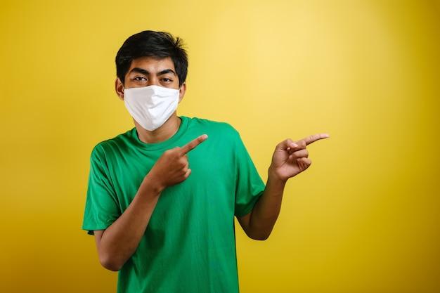Porträt eines gutaussehenden jungen asiatischen mannes, der eine medizinische schutzmaske trägt und mit dem finger auf den seitlichen kopierraum zeigt. konzept der bekämpfung des coronavirus covid-19 vor gelbem hintergrund