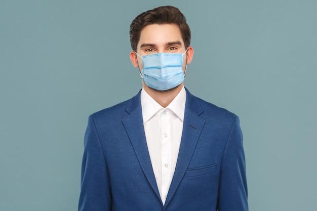 Porträt eines gutaussehenden jungen geschäftsmannes mit chirurgischer medizinischer maske, der in die kamera schaut