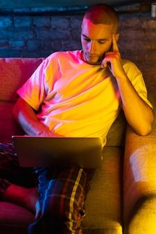 Porträt eines gutaussehenden jungen kaukasischen mannes, der zu hause in einem neonorangefarbenen beleuchteten raum sitzt.