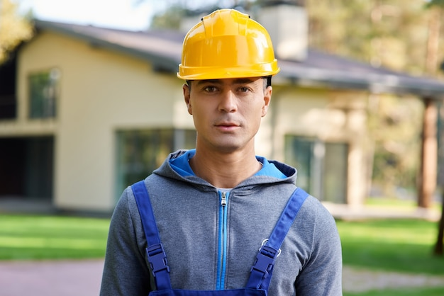 Porträt eines gutaussehenden jungen männlichen ingenieurs mit schutzhelm, der die kamera betrachtet, die im freien posiert, während
