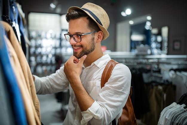 Porträt eines gutaussehenden jungen mannes, der kleidung im geschäft kauft