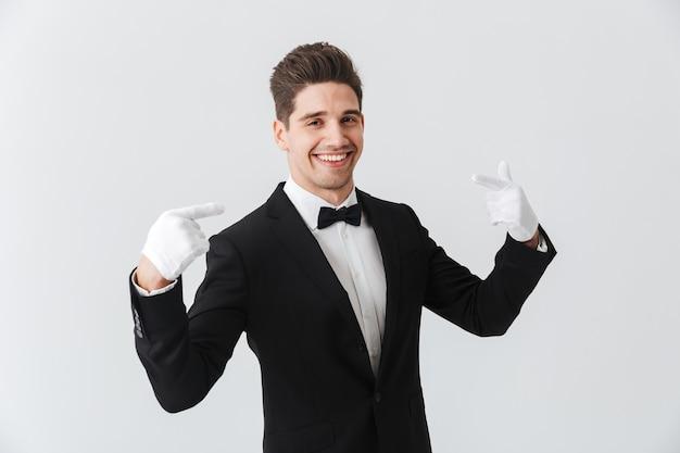 Porträt eines gutaussehenden jungen mannes kellner, der smoking und handschuhe trägt, die isoliert über weißer wand stehen und auf sich selbst zeigen
