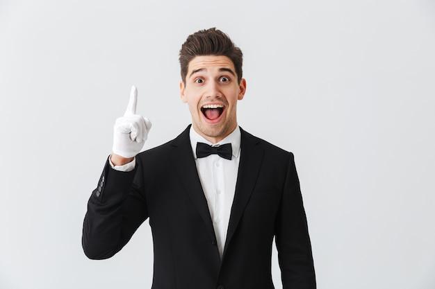 Porträt eines gutaussehenden jungen mannes kellner, der smoking und handschuhe trägt, die isoliert über weißer wand stehen und nach oben zeigen