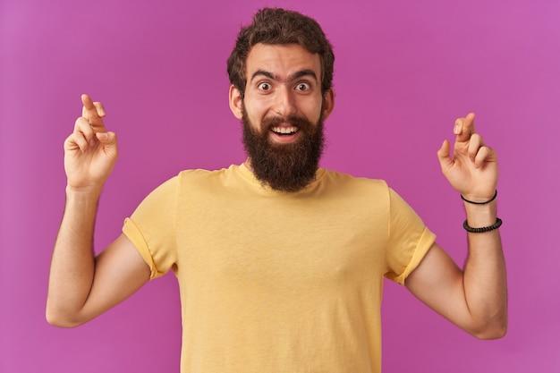 Porträt eines gutaussehenden jungen mannes mit armen zeigt mit gekreuzten fingern nach oben emotionen überrascht glückliches gesicht frohes lächeln