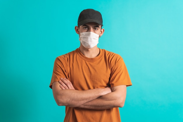 Porträt eines gutaussehenden jungen mannes mit chirurgischer medizinischer maske, der in die kamera schaut