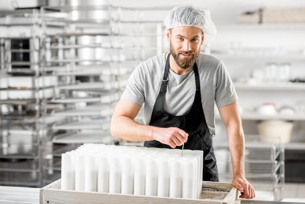 Porträt eines gutaussehenden käsers in uniform, der auf dem kleinen produzierenden bauernhof käse zu formen formt