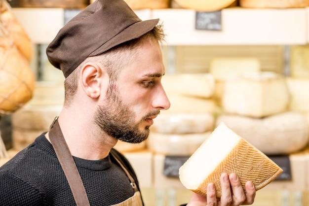 Porträt eines gutaussehenden käseverkäufers in uniform, der nach gereiftem käse riecht, vor der ladenvitrine voller verschiedener käsesorten