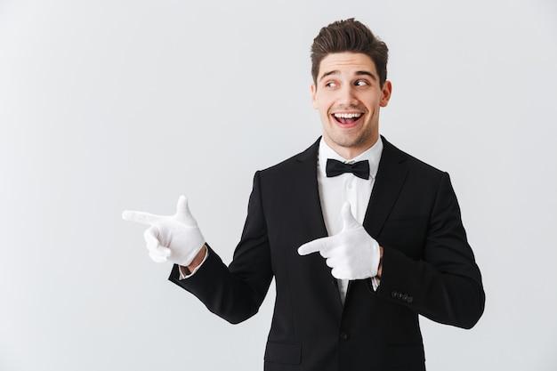 Porträt eines gutaussehenden kellners des jungen mannes, der smoking und handschuhe trägt, die lokal über weißer wand stehen und finger auf kopierraum zeigen