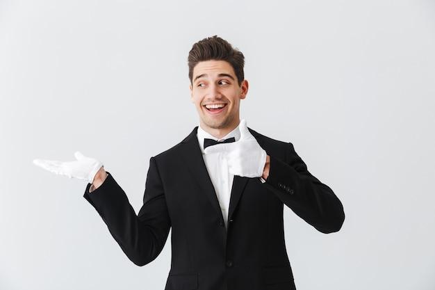 Porträt eines gutaussehenden kellners des jungen mannes, der smoking und handschuhe trägt, die lokal über weißer wand stehen und kopienraum präsentieren
