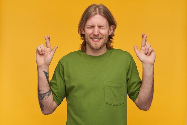 Porträt eines gutaussehenden, konzentrierten mannes mit blonder frisur und bart. grünes t-shirt tragen. hat tätowierung. drückt die daumen, wünscht es euch mit geschlossenen augen. stehen sie isoliert über gelber wand