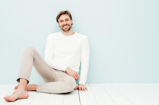 Porträt eines gutaussehenden lächelnden hipster-lumbersexual-geschäftsmann-modells, das einen lässigen weißen pullover und eine hose trägt