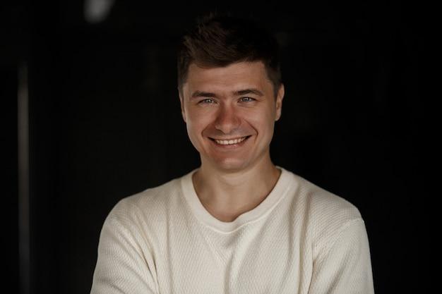 Porträt eines gutaussehenden, lächelnden, positiven mannes in einem weißen t-shirt in einem dunklen raum.