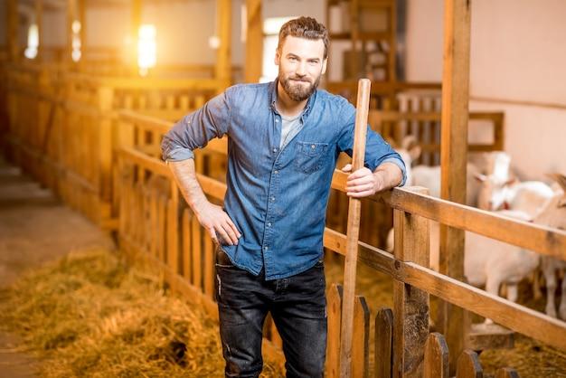 Porträt eines gutaussehenden landwirts, der mit gabel am ziegenstall steht. natürliche milchproduktion und landwirtschaft