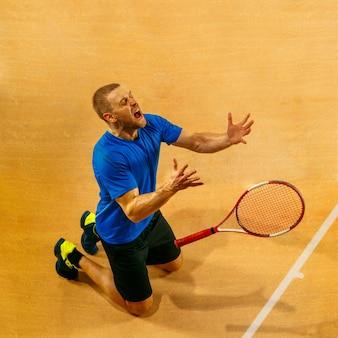 Porträt eines gutaussehenden männlichen tennisspielers, der seinen erfolg auf einer hofwand feiert