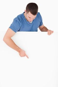 Porträt eines gutaussehenden mannes, der auf eine leerplatte zeigt