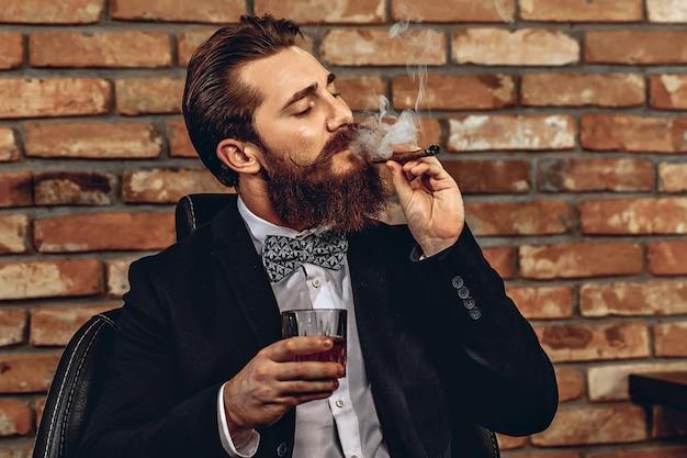 Porträt eines gutaussehenden mannes, der auf einem stuhl sitzt und ein glas whisky in der hand hält und eine braune zigarre raucht