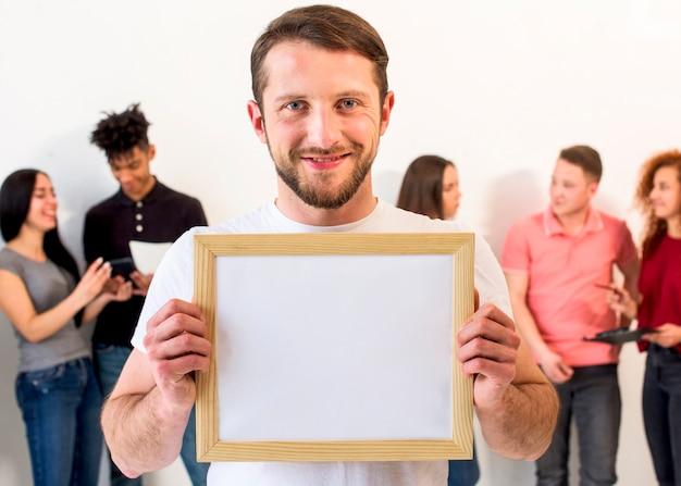 Porträt eines gutaussehenden mannes, der den leeren bilderrahmen betrachtet kamera hält