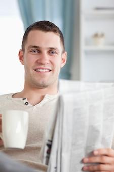 Porträt eines gutaussehenden mannes, der einen kaffee beim lesen das neue trinkt