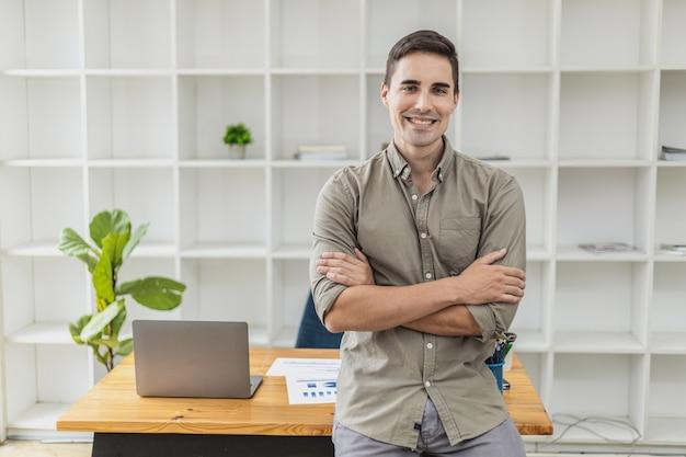 Porträt eines gutaussehenden mannes, der mit verschränkten armen in seinem büro steht. das konzept einer neuen generation von geschäftsleuten, ein startup-unternehmen zu gründen, um das geschäft kompetent und mit wachstum zu führen