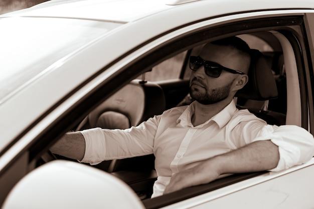 Porträt eines gutaussehenden mannes, der sein auto fährt, bärtiger mann mit stil und status