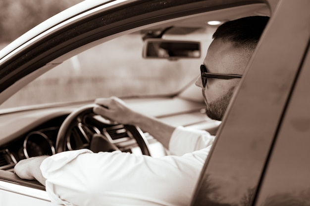 Porträt eines gutaussehenden mannes, der sein auto fährt bärtiger mann mit stil und status