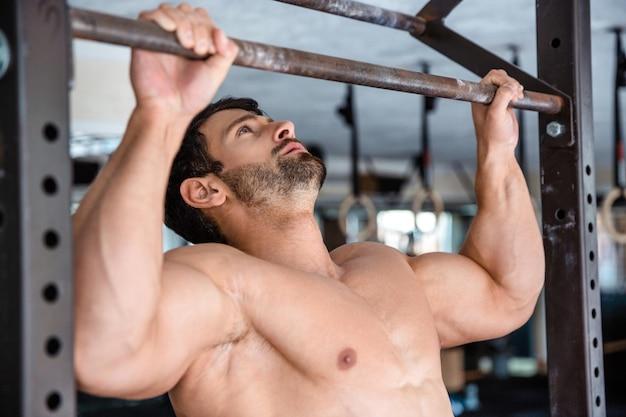Porträt eines gutaussehenden mannes, der sich im fitnessstudio an der reckstange festzieht