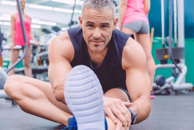 Porträt eines gutaussehenden mannes, der sich in einem fitnesscenter ausdehnt, und einer schönen frau, die übungen mit hanteln im hintergrund macht