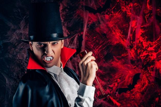 Porträt eines gutaussehenden mannes, gekleidet in einem dracula-kostüm für halloween. vampir hält ein glas blut
