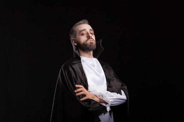 Porträt eines gutaussehenden mannes, gekleidet in einem dracula-kostüm für halloween. vampirzähne. beängstigender dämon.