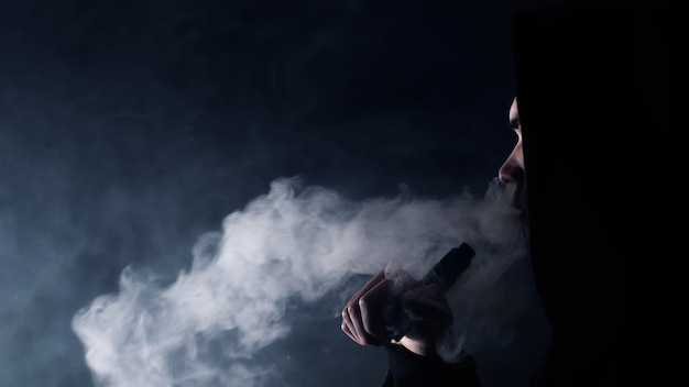 Porträt eines gutaussehenden mannes in einem schwarzen hut und einer sonnenbrille, die eine dampfwolke von einer e-zigarette verdampfen und ausatmen