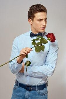 Porträt eines gutaussehenden mannes mit einer roten rose in seinen händen
