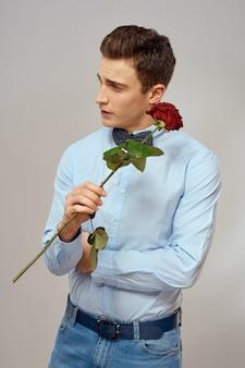 Porträt eines gutaussehenden mannes mit einer roten rose