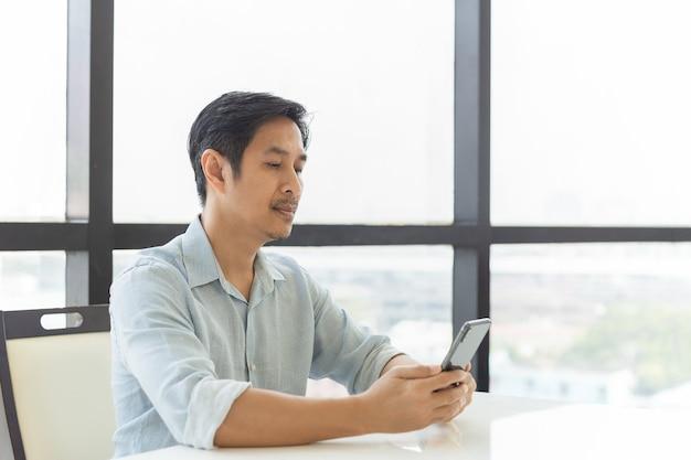 Porträt eines gutaussehenden mannes mit smartphone im büro