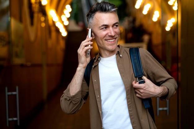 Porträt eines gutaussehenden mannes mit smartphone in der stadt