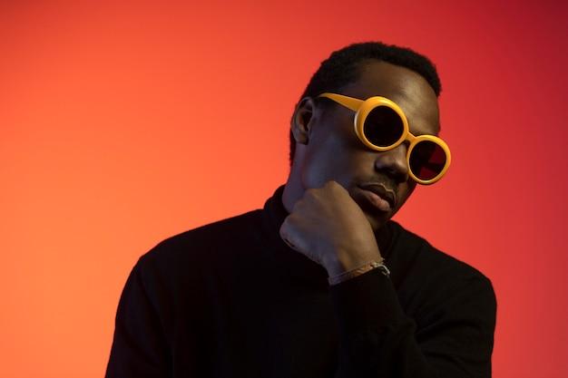Porträt eines gutaussehenden mannes mit sonnenbrille über orangefarbenem hintergrund